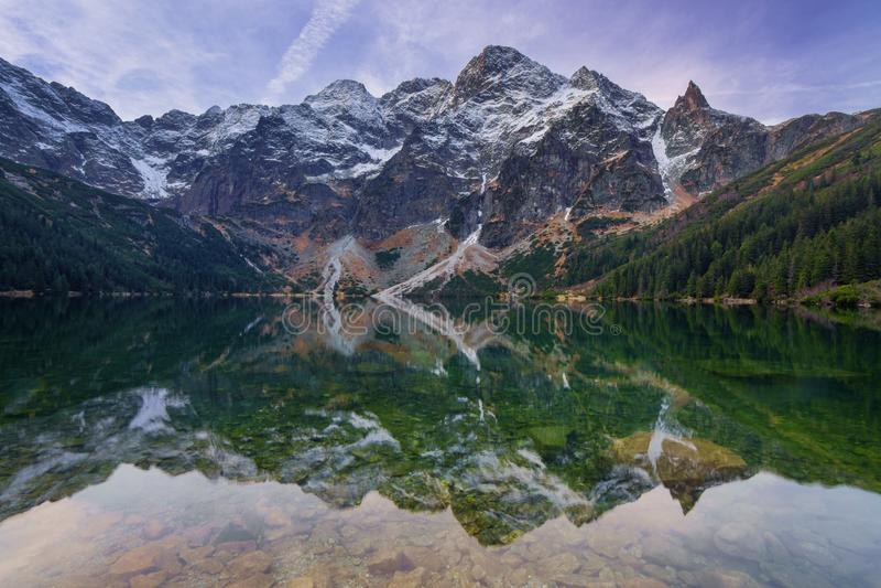 Отражение скалистых гор в спокойной воде озера стоковые фотографии rf