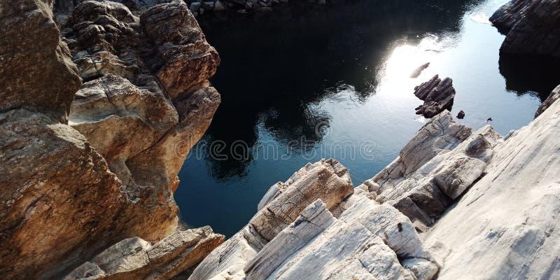 Отражение Солнца на воде с утесами или горой стоковые изображения rf