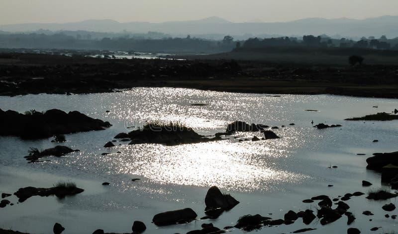 Отражение Солнця от холмистой речной воды стоковые фотографии rf
