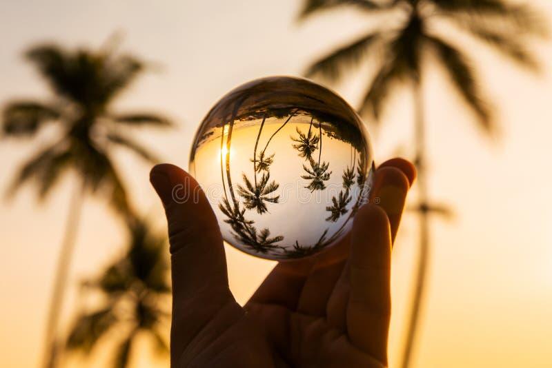 Отражение тропического пляжа на заходе солнца в стеклянном шарике стоковое изображение rf