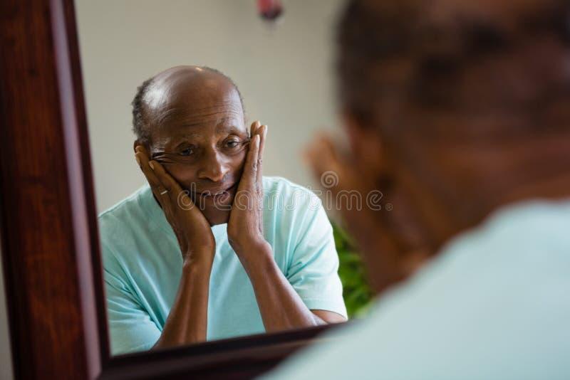 Отражение concerned старшего человека на зеркале стоковое фото rf