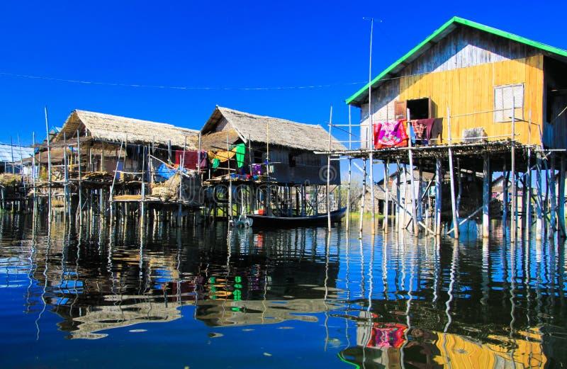 Отражения домов традиционных ходулей деревянных в ровном как стеклянная вода сравнивая с безоблачным голубым небом стоковая фотография