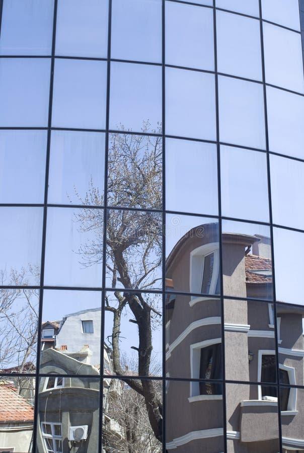 Отражения домов и деревьев в новом стеклянном здании стоковая фотография rf
