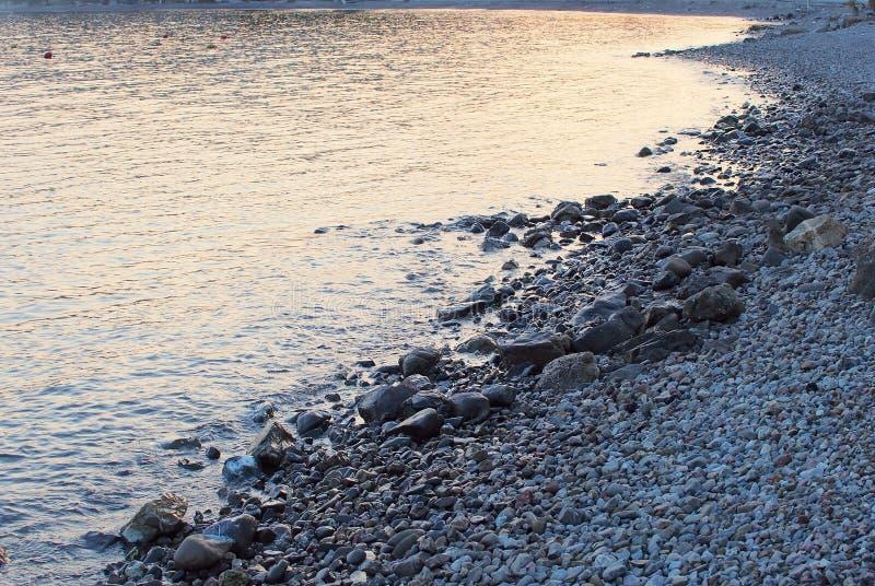 Отражения сумрака на скалистом пляже, Греции стоковая фотография rf