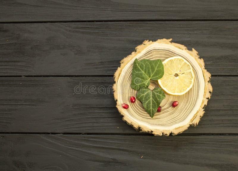 Отрежьте древесину с с кусками ягод лимона и гранатового дерева стоковое фото