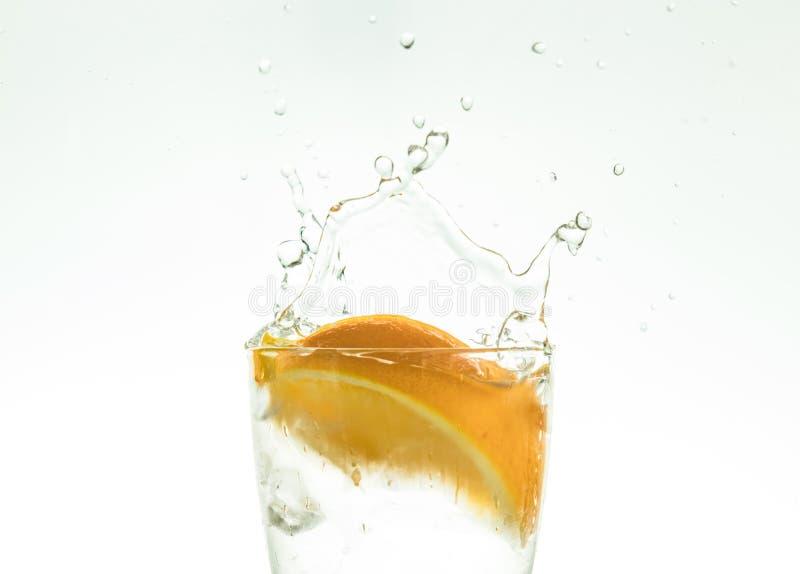 Отрежьте оранжевый кусок в стекле воды и сделайте брызги на белой предпосылке брызги воды в воздухе кусок падений цитруса стоковая фотография rf