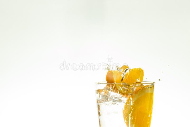 Отрежьте оранжевый кусок в стекле воды и сделайте брызги на белой предпосылке брызги воды в воздухе кусок падений цитруса стоковые изображения rf
