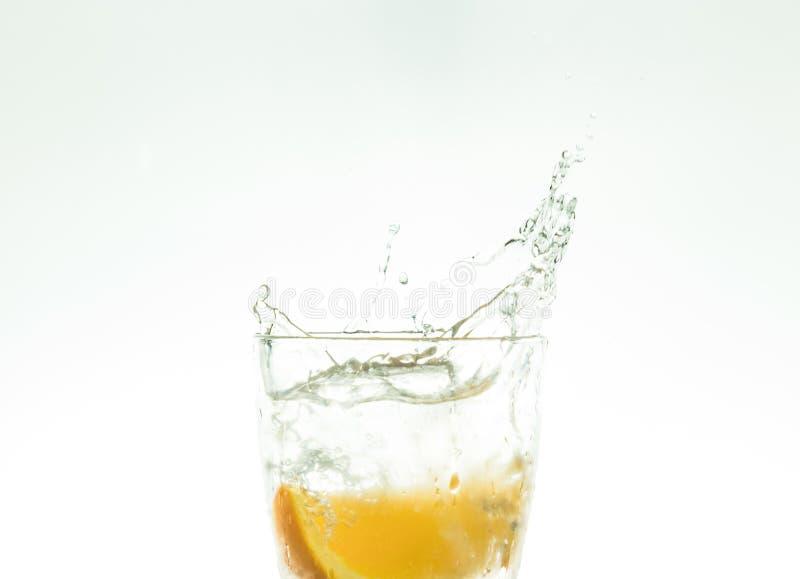 Отрежьте оранжевый кусок в стекле воды и сделайте брызги на белой предпосылке брызги воды в воздухе кусок падений цитруса стоковые изображения