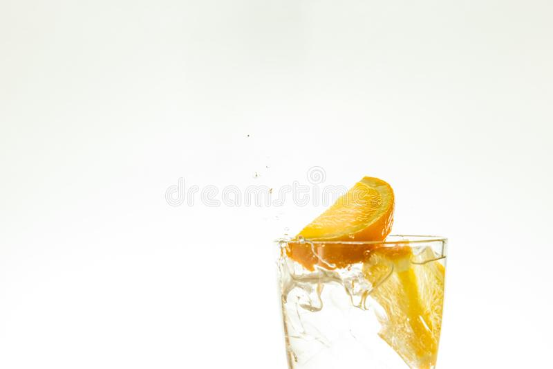 Отрежьте оранжевый кусок в стекле воды и сделайте брызги на белой предпосылке брызги воды в воздухе кусок падений цитруса стоковые фотографии rf