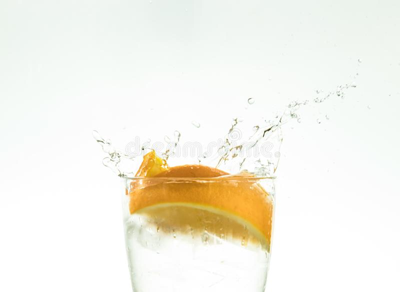 Отрежьте оранжевый кусок в стекле воды и сделайте брызги на белой предпосылке брызги воды в воздухе кусок падений цитруса стоковое изображение rf