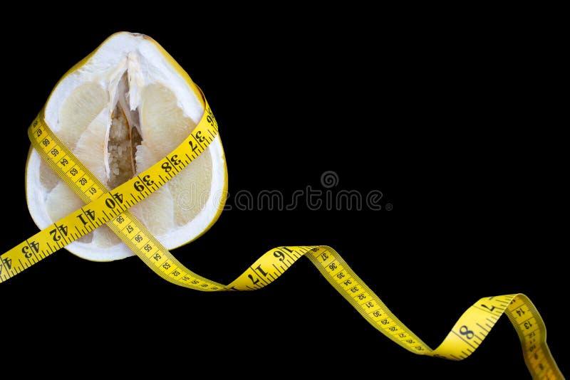 Отрежьте плод pamello с сочной пульпой в оболочке с измеряя лентой с сантиметрами и дюймами на черной предпосылке стоковые изображения