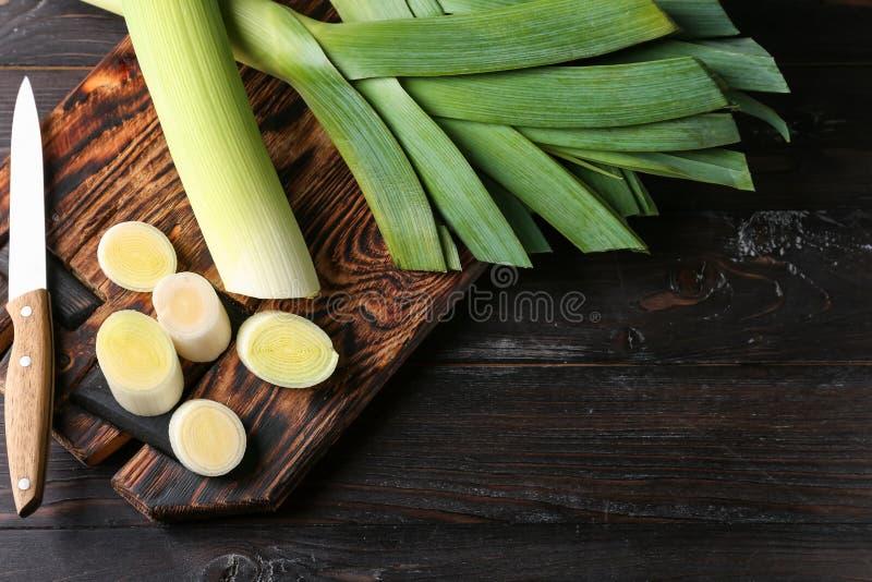 Отрежьте свежие лук-пореи на деревянной доске стоковая фотография rf