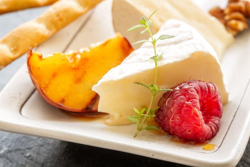 Отрежьте сыр камамбера с зажаренным персиком, свежими полениками и стоковые фото