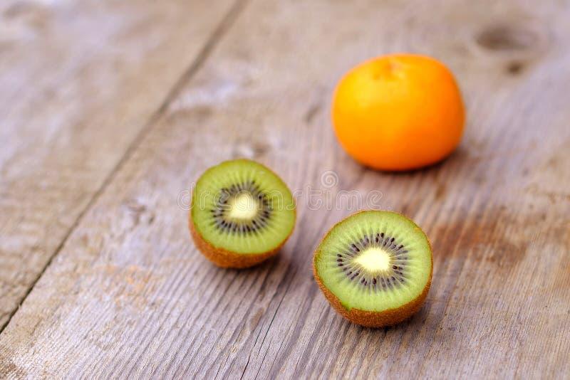 2 отрезали кивиы и один апельсин на деревянной доске сделанной сосны стоковая фотография
