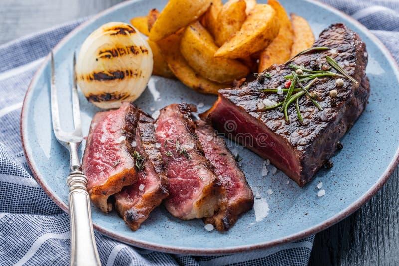 Отрезанная зажаренная говядина стейка Средство стейка говядины с картошкой и fr стоковые фотографии rf