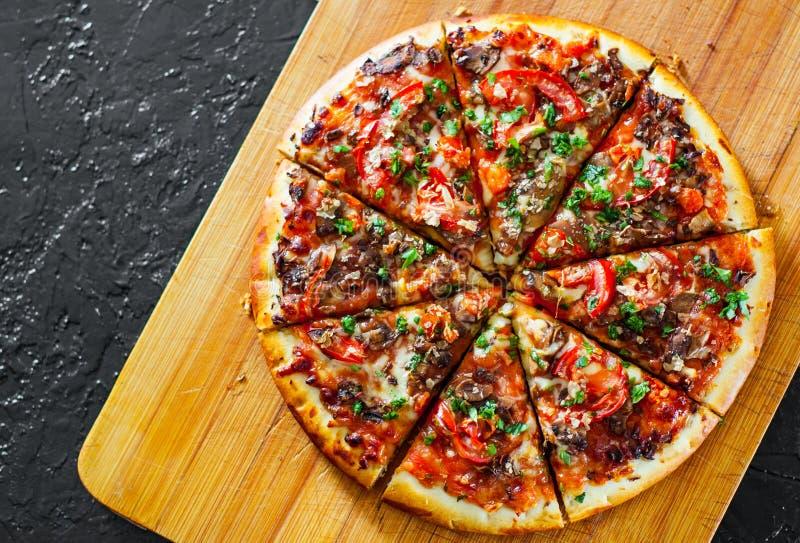 Отрезанная пицца с сыром моццареллы, грибами, томатами, перцем, специями и свежим базиликом стоковое фото rf