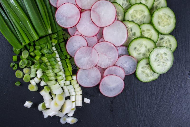 Отрезанная редиска, огурец, зеленый лук на черной доске шифера Ингридиенты для салата весны витамина стоковые изображения