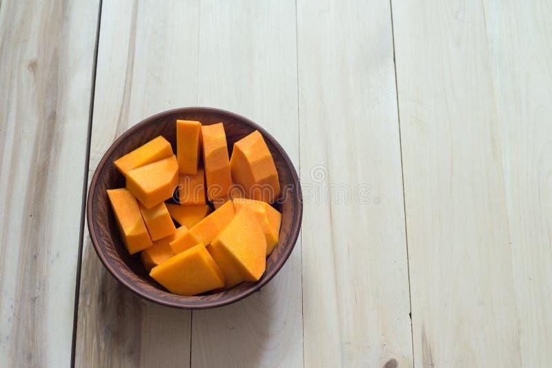 Отрезанная сырцовая оранжевая тыква на деревянной разделочной доске стоковые изображения rf