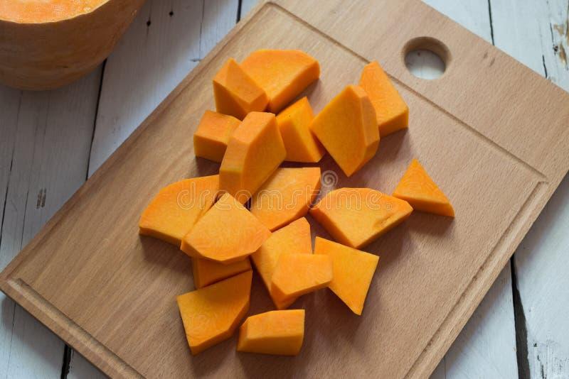 Отрезанная сырцовая оранжевая тыква на разделочной доске стоковое фото rf