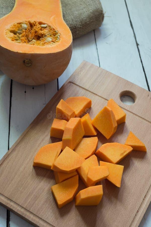 Отрезанная сырцовая оранжевая тыква на разделочной доске стоковое изображение