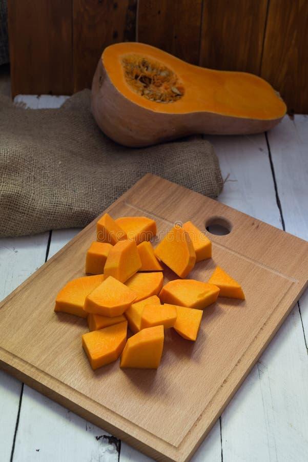 Отрезанная сырцовая оранжевая тыква на разделочной доске стоковые изображения