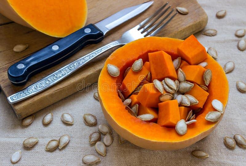 Отрезанная сырцовая оранжевая тыква Нож и вилка на деревянном режа bo стоковая фотография