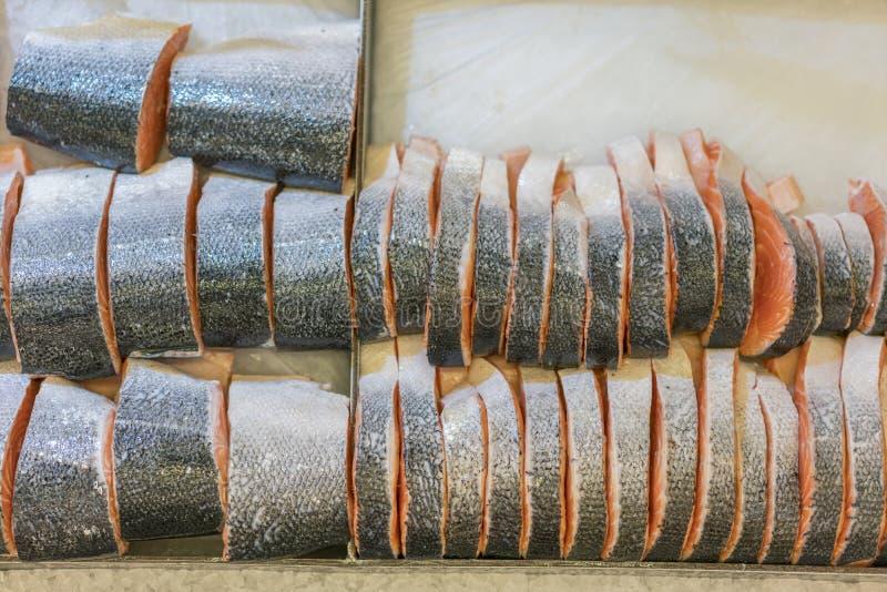 Отрезанное сырцовое, сваренные семги, красные рыбы, лежа в льде на счетчике в супермаркете рыбы свежие Стейки красных рыб на льде стоковые фото