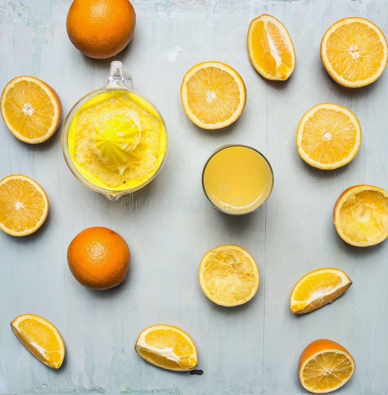 Отрезанные апельсины, juicer, стекло конца взгляд сверху предпосылки сока деревянного деревенского вверх стоковые изображения rf