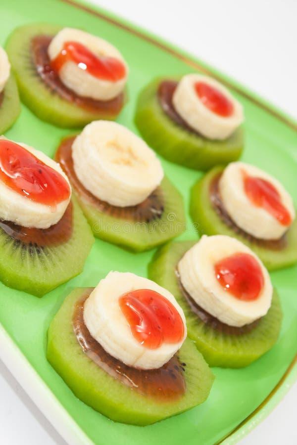 Отрезанные банан и киви с сиропом клубники на зеленой плите стоковые изображения