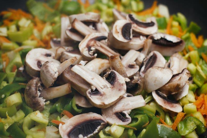 Отрезанные грибы champignon с перцами и томатами Зажаренное блюдо в лотке стоковое фото