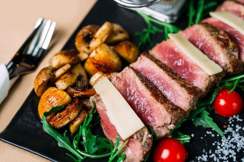 Отрезанные зажаренные стейк и салат барбекю говядины с томатами и arugula стоковые фото