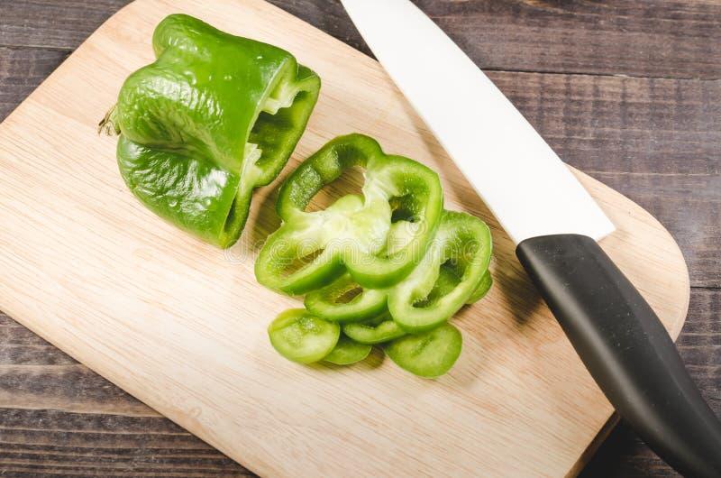 Отрезанные зеленые перец паприки/перцы отрезать на деревянной разделочной доске с белым ножом с черной ручкой стоковые фото