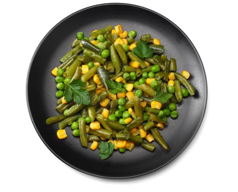 отрезанные зеленые фасоли, зеленые горохи и мозоль на черной плите изолированной на белой предпосылке Взгляд сверху еда здоровая стоковая фотография