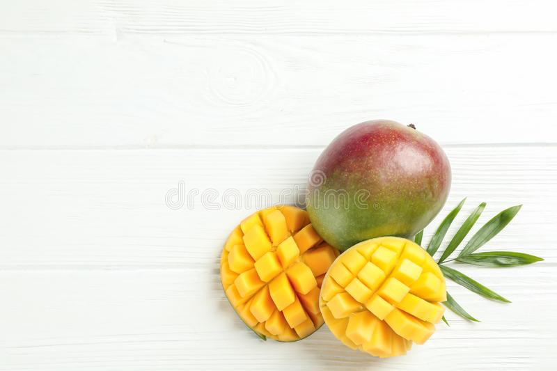 Отрезанные зрелые манго и лист ладони на белой предпосылке стоковые фотографии rf