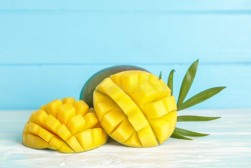 Отрезанные зрелые манго и лист ладони на белой таблице против предпосылки цвета стоковые фотографии rf
