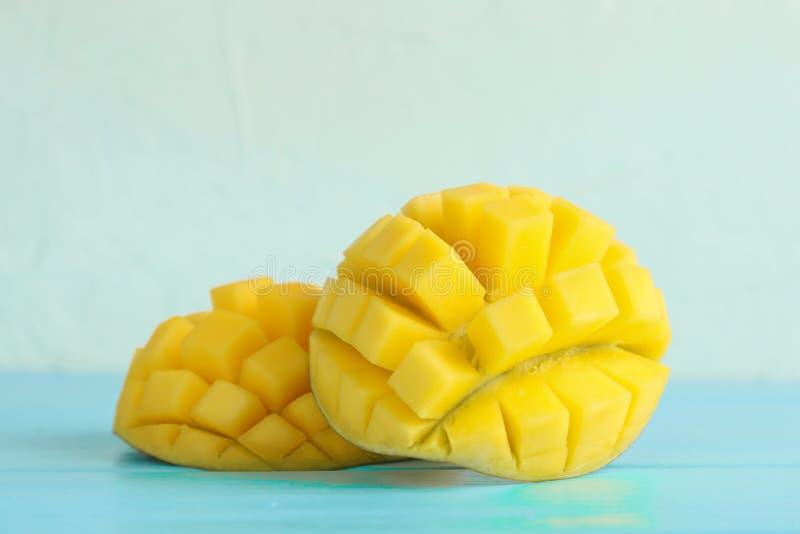 Отрезанные зрелые манго на таблице цвета против белой предпосылки стоковые изображения