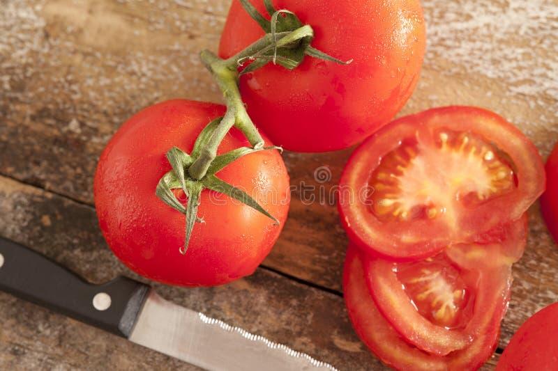 Отрезанные и все свежие томаты на лозе стоковое фото rf