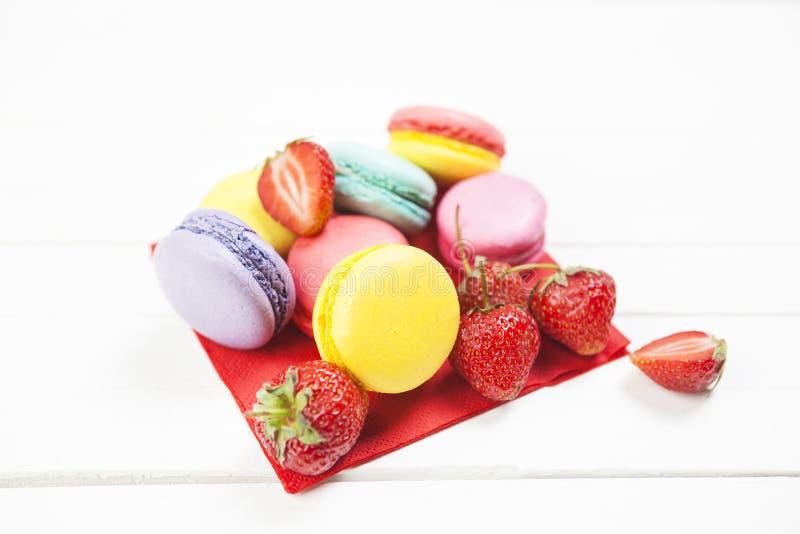 Отрезанные клубники ¹ ¬â€ 'â⠹ ¬â€ 'ââ и печенья macaroon на белой таблице с салфеткой лето с клубниками и ярким co стоковые фотографии rf