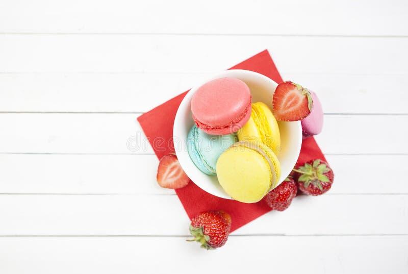 Отрезанные клубники ¹ ¬â€ 'â⠹ ¬â€ 'ââ и печенья macaroon на белой таблице с салфеткой лето с клубниками и ярким co стоковые изображения