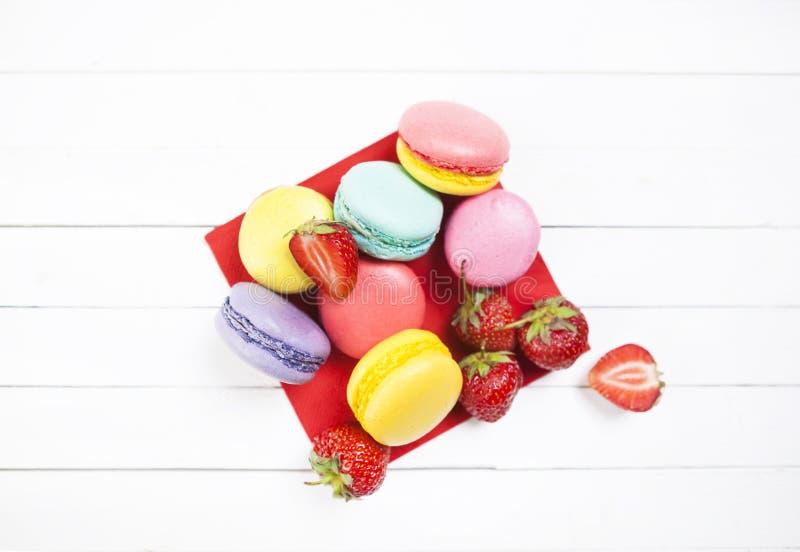 Отрезанные клубники ‹â€ ‹â€ и печенья macaroon на белой таблице с салфеткой лето с клубниками и ярким co стоковые фото