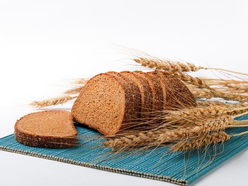 Отрезанные колоски хлеба и пшеницы на бамбуковой циновке Белая предпосылка стоковое изображение rf