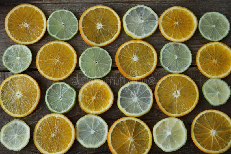 Отрезанные кольца апельсина, лимона, известки на деревянной предпосылке E , вытрезвитель, диета стоковая фотография