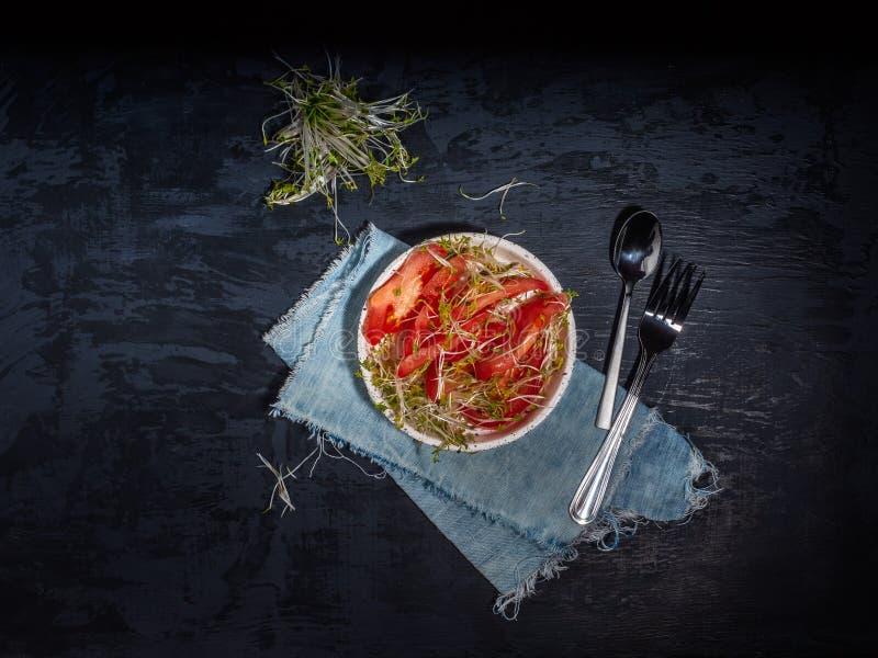 Отрезанные красные томаты и и листья на темной предпосылке, крупный план cresscalata Керамическая салфетка плиты, столового прибо стоковое фото