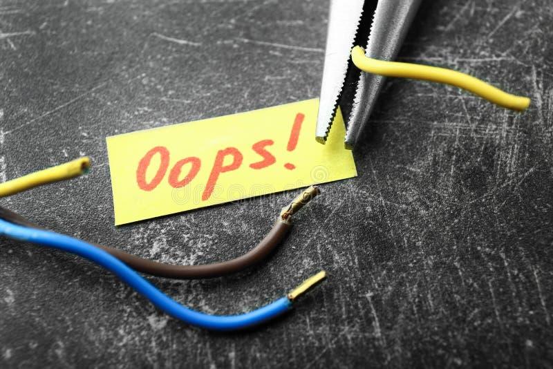 Отрезанные провода и кусок бумаги с отправляют SMS OOPS на серой предпосылке Концепция ошибки стоковые фото