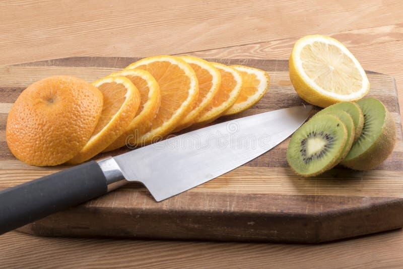 Отрезанный апельсин с плодоовощ и лимоном кивиа на прерывая доске стоковые фото