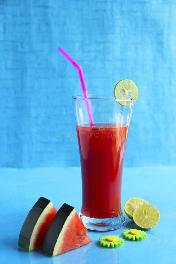 Отрезанный арбуз и сок украшенные при лимон, изолированный на свете - голубой предпосылке стоковые изображения