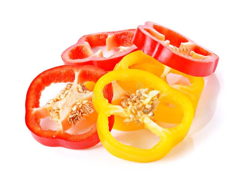 Отрезанный красный и желтый перец изолированный на белизне стоковые фото