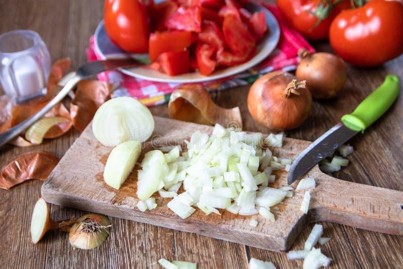 Отрезанный лук на доске кухни, весь лук и томаты на заднем плане стоковые фото