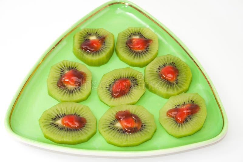 Отрезанный плодоовощ кивиа с соусом клубники на зеленой плите стоковое изображение rf