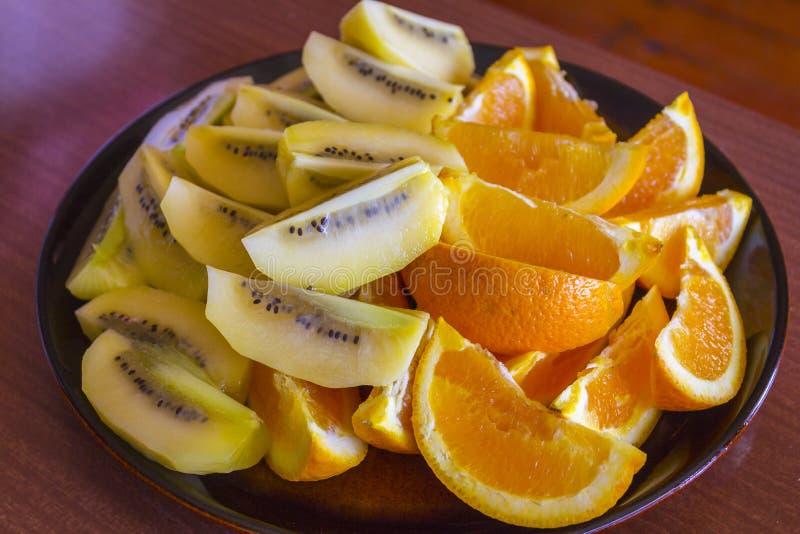 Отрезанный свежий апельсин и золотой плодоовощ кивиа на плите; Окленд Новая Зеландия стоковые изображения